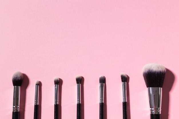 Vários pincéis de maquiagem em fundo rosa com cosméticos de vista superior do espaço de cópia e conceito de beleza