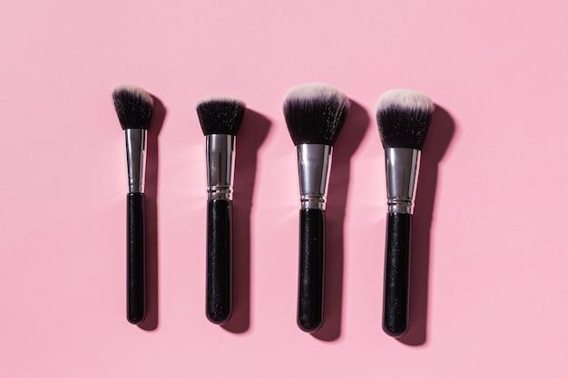 Vários pincéis de maquiagem em fundo rosa, vista superior. cosméticos e conceito de beleza.
