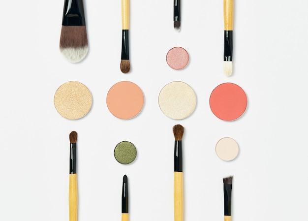 Vários pincéis de maquiagem profissionais com cabo marrom, dispostos simetricamente sobre um fundo branco, em torno de uma variedade de paletas de sombras redondas multicoloridas. conceito de beleza e maquiagem, maquiador.