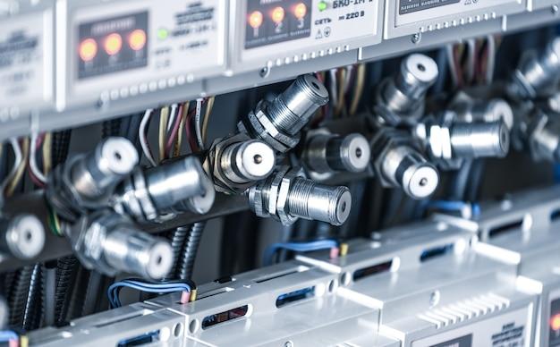 Vários plugues de metal estão pendurados próximos aos painéis de instrumentos em uma fábrica para a produção de equipamentos especializados. conceito de manufatura industrial
