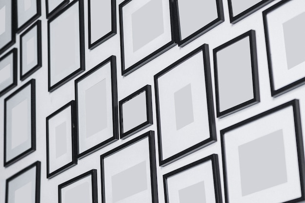 Vários porta-retratos em branco na parede branca
