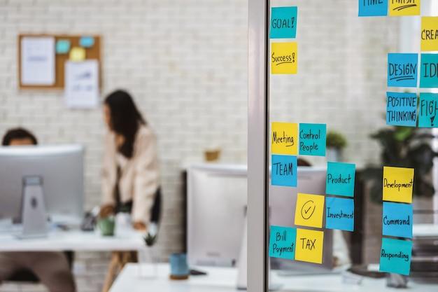 Vários post-it com palavras de estratégia de negócios na parede de vidro do escritório