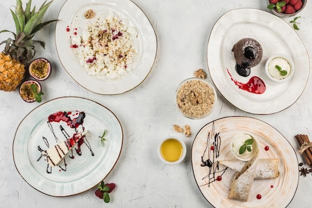 Vários pratos com sobremesas em pratos, cheesecake, muffin de chocolate, strudel e requeijão servidos pelo chef, vista de cima com uma cópia de espaço. colocação plana. o conceito de café da manhã. comida do restaurante.