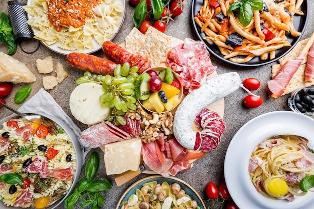 Vários pratos de massa com diferentes tipos de molhos e diversos petiscos e aperitivos sobre pedra.