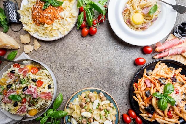 Vários pratos de massa com diferentes tipos de molhos sobre pedra. conceitos de comida italiana.