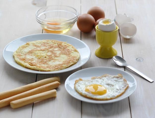 Vários pratos de ovos uma omelete, um ovo em uma bagunça
