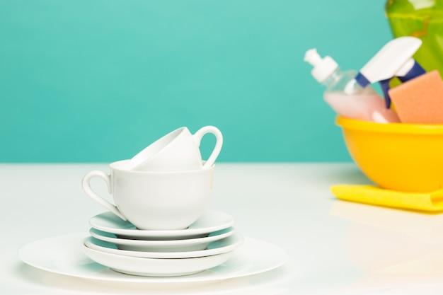 Vários pratos, esponjas de cozinha e garrafas de plástico com sabão líquido para lavar louça