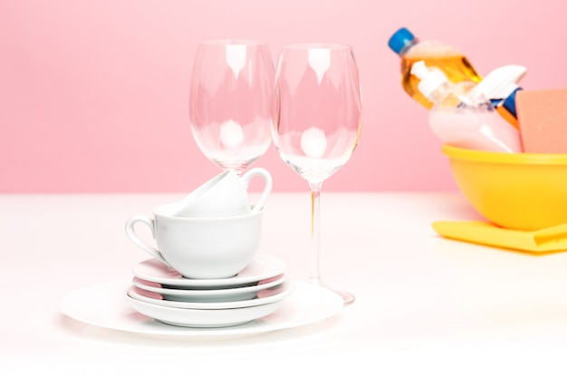 Vários pratos, esponjas de cozinha e garrafas plásticas com sabão líquido natural para lavar louça em uso na lavagem manual.