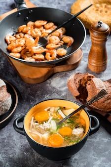 Vários pratos na mesa: sopa de almôndegas, pão, camarão frito.