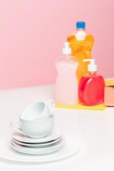 Vários pratos, uma esponja de cozinha e uma garrafa de plástico com sabão líquido para lavar louça
