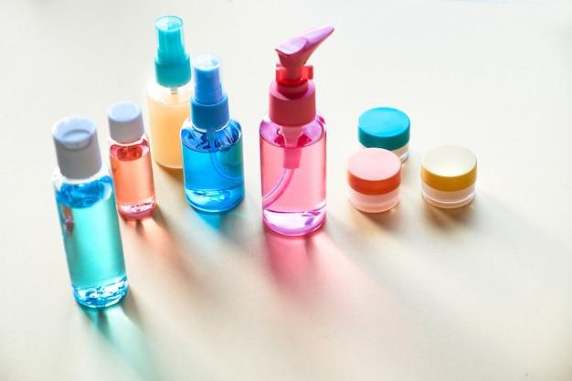 Vários produtos cosméticos em frascos de viagem de plástico transparente com longas sombras, cópia-espaço