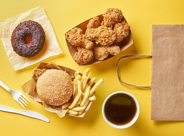 Vários produtos de fast food e sacola de papel em fundo amarelo, vista superior