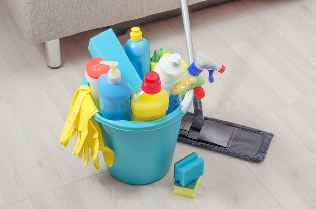Vários produtos de limpeza com guardanapos, esponjas e luvas em um balde azul na sala.