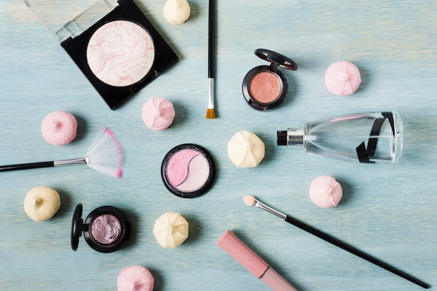 Vários produtos de maquiagem ao lado de doces