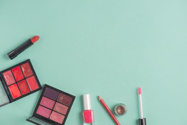 Vários produtos de maquiagem em fundo verde