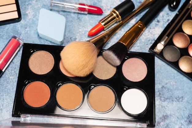 Vários produtos de maquiagem, pincéis em fundo azul