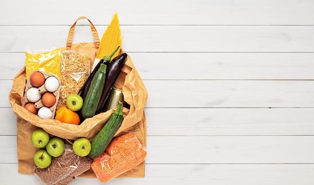 Vários produtos de mercearia em uma sacola de papel reutilizável