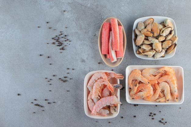 Vários produtos do mar em taças, no fundo de mármore.