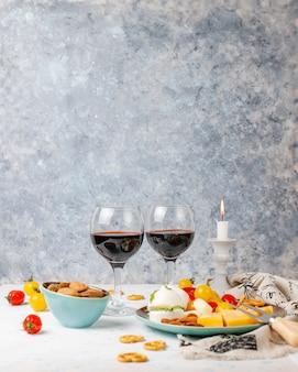 Vários queijo e queijo prato na mesa de luz com diferentes nozes e frutas e copo de vinho