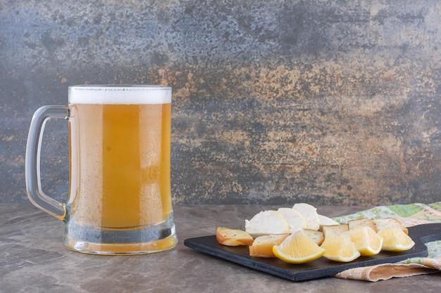 Vários queijo e rodelas de limão no tabuleiro escuro com cerveja
