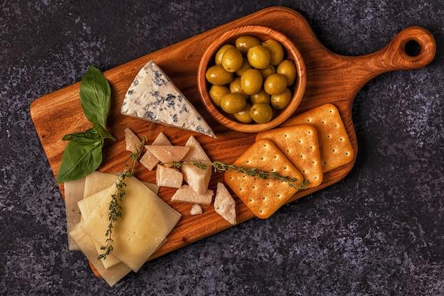 Vários queijos com bolachas e azeitonas em tabuleiro