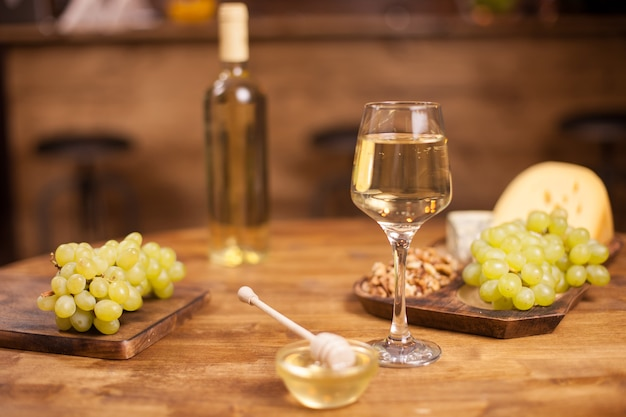 Vários queijos com uma garrafa e um copo de vinho sobre fundo amarelo. uvas deliciosas e frescas. mel saboroso.