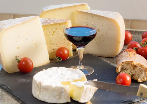 Vários queijos franceses com copo de vinho tinto