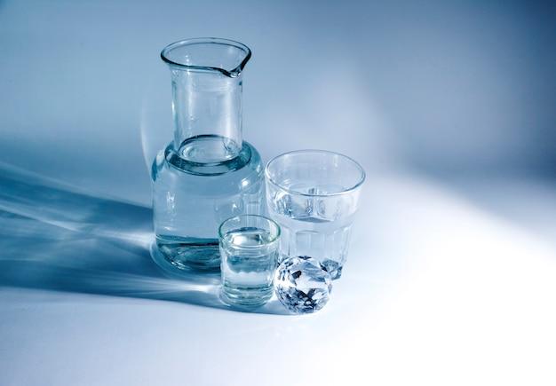 Vários recipientes de material de vidro com diamante brilhante sobre fundo azul