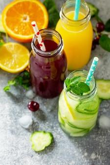 Vários refrescos bebidas desintoxicação pepino água suco de cereja e suco de laranja copiar espaço