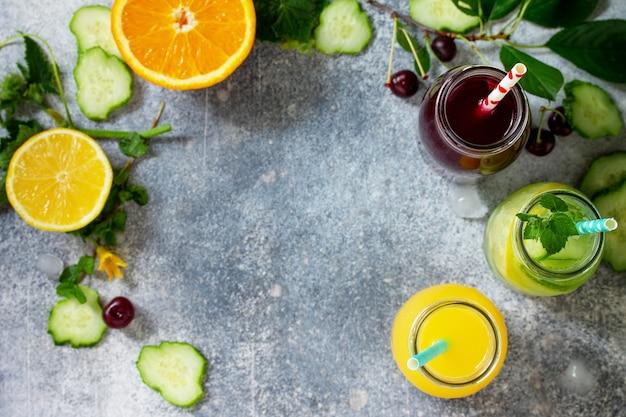 Vários refrescos bebidas desintoxicação pepino água suco de cereja e suco de laranja vista superior