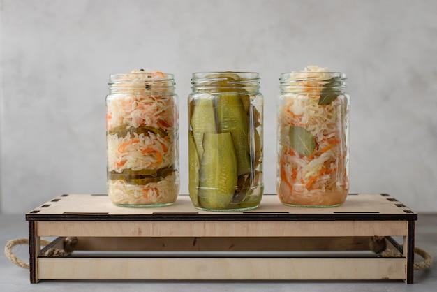 Vários repolho fermentado e pepino em frascos em uma superfície de caixa de madeira cinza,