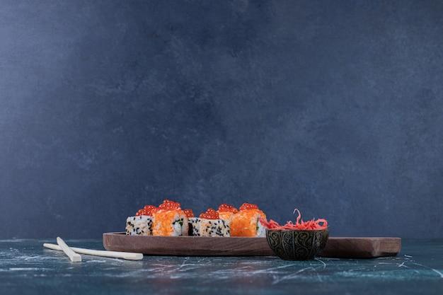 Vários rolos de sushi decorados com caviar vermelho e pauzinhos.