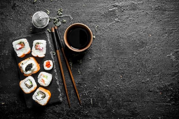 Vários rolos japoneses com molho de soja e pauzinhos. em preto rústico