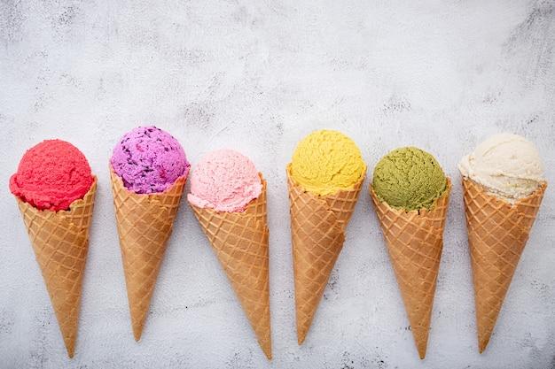 Vários sabores de sorvete em cones configurados em fundo de pedra branca