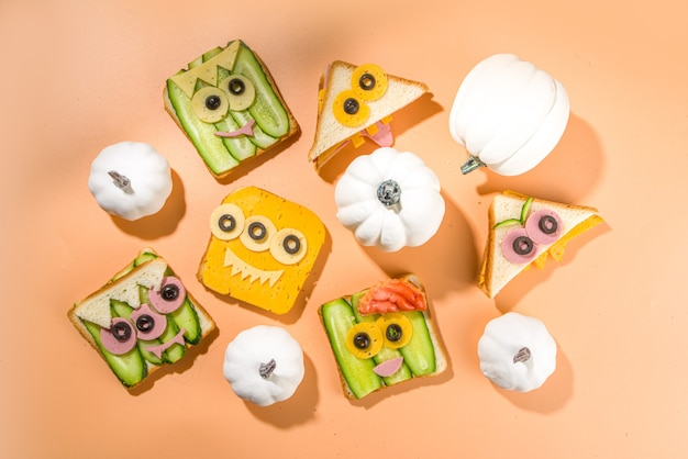 Vários sanduíches de halloween de monstro engraçado. conjunto de lanches criativos de torradas com queijo, comida de festa infantil de halloween, vista de cima