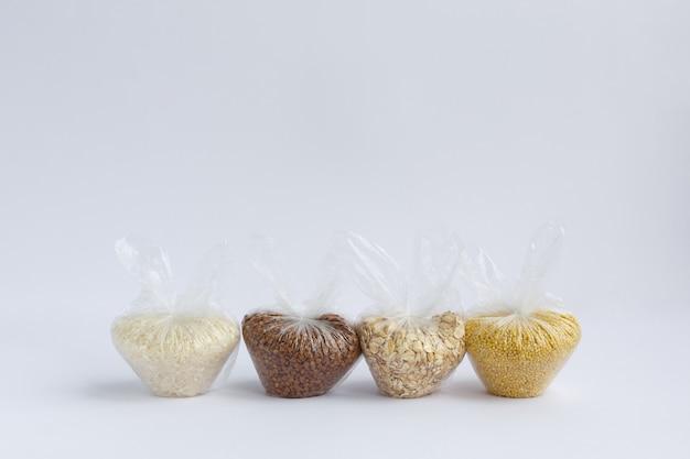 Vários sêmolas em pequenos sacos plásticos. arroz e farinha de aveia, trigo sarraceno e painço