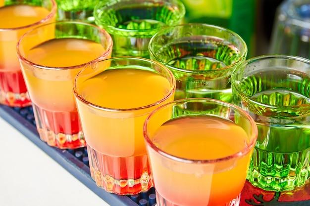 Vários shots de bebidas alcoólicas multicoloridas no balcão do bar