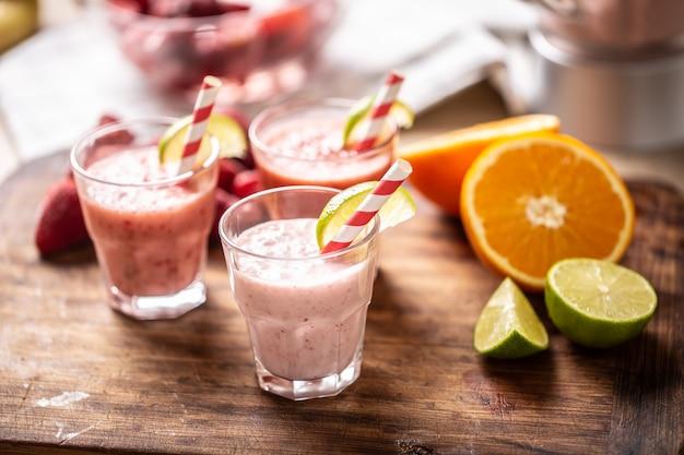Vários smoothies de frutas em copos de vidro com canudos de papel e rodelas de limão e mais frutas cítricas ao lado.