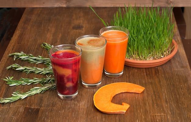 Vários sucos de vegetais espremidos na hora com o pedaço de abóbora e trigo em germinação em uma mesa de madeira.