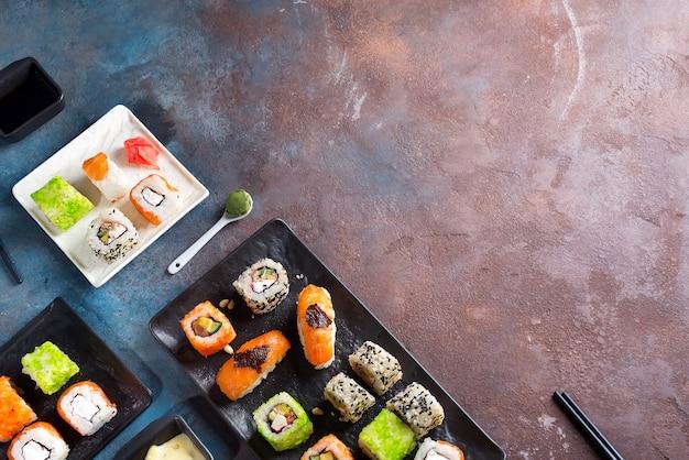 Vários sushi conjunto na placa com varas de ardósia, molho de pedra duotone