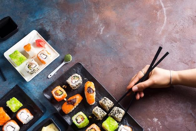 Vários sushi definido na placa, mão com varas de ardósia, molho no fundo de pedra