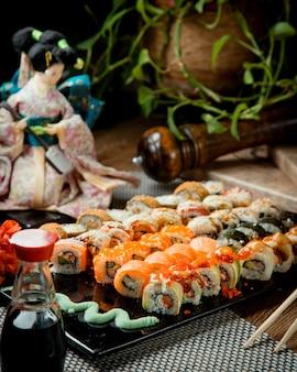 Vários sushi em uma bandeja com wasabi e molho de soja