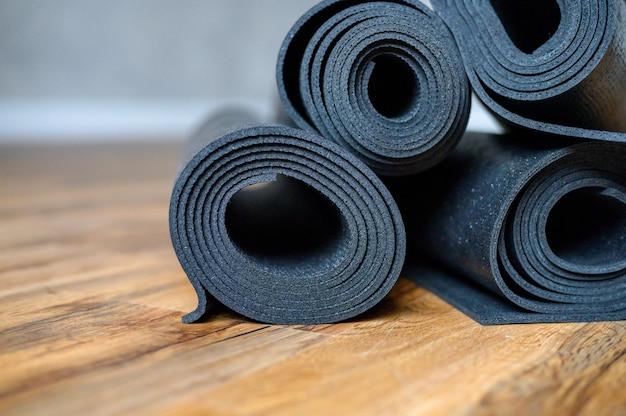Vários tapetes enrolados de borracha para ioga ou fitness de cor preta no chão de madeira. acessórios esportivos