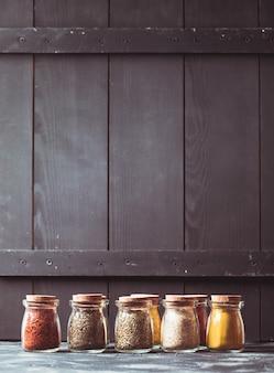 Vários temperos moídos em garrafas de vidro vintage, lugar para texto