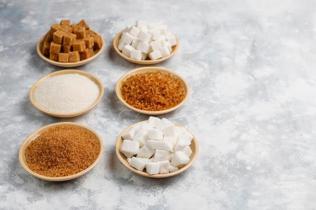 Vários tipos de açúcar, açúcar mascavo e branco no concreto, vista superior