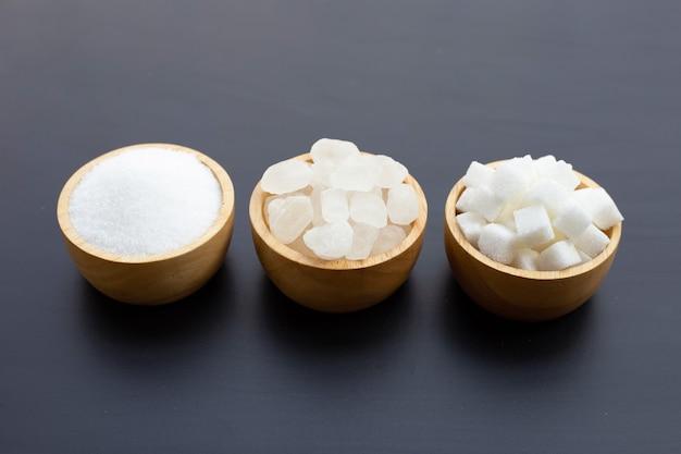 Vários tipos de açúcar em fundo escuro.