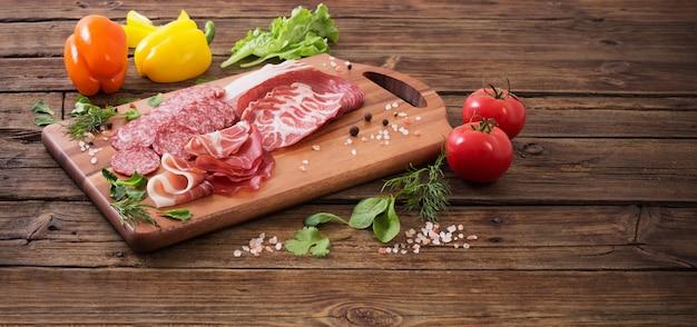 Vários tipos de carne e legumes na mesa de madeira