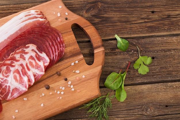 Vários tipos de carne e salsichas na mesa de madeira