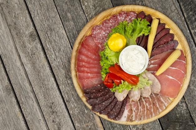 Vários tipos de carne em uma placa de madeira. vista superior, espaço de texto