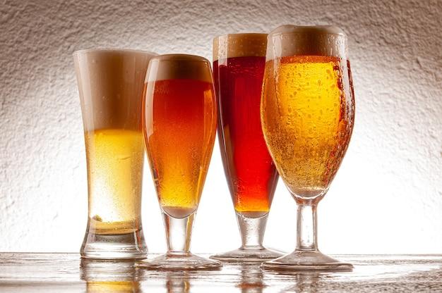 Vários tipos de cervejas servidas em copos e canecas de cristal